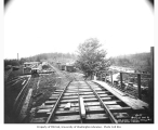 Railroad logging camp from tracks, showing automobiles, speeder and bunkhouses, Mutual Lumber...