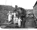 Mess hall crew and train crew in front of a rod locomotive at a railroad camp, Polson Logging...