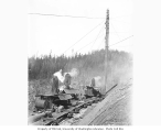Donkey engines and skeleton railroad log cars being loaded, with injured man receiving first aid,...