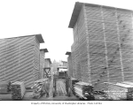 Man (probably Thomas or Russell Bordeaux) and gas lumber carrier amid stacks of lumber, Mumby...