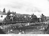 Railroad track repair crew on flatcar with St. Paul and Tacoma Lumber Company's three-truck Shay...