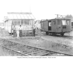 Saw filers outside workshop at railroad camp, with speeder, St. Paul and Tacoma Lumber Company,...