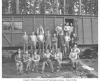 Logging crew at railroad car mess hall, with Clark Kinsey photographs piled to one side, Vance...