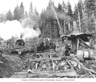 Logging crew at loading operation, with skeleton railroad cars and two donkey engines, Waite Mill...
