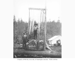 Loggers with assortment of saws standing on stump which reads LLLL (for Loyal Legion of Loggers...