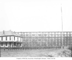 Spruce Division soldiers in front of boarding house and high railroad trestle bridge, camp 7E, ca....