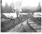 Crew at camp, with locomotive and cars, ca. 1918