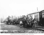 Asian crew on flatbed railroad car being pushed by Snoqualmie Falls Lumber Company's Climax...