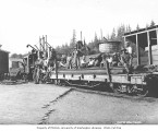 Asian construction crew on flatbed railroad car pushed by Snoqualmie Falls Lumber Company's Climax...