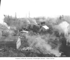 Railroad logging camp showing three locomotives and crew returning to camp, Stimson Logging...
