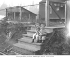 Boys sitting on steps at railroad logging camp, ca. 1928