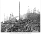 Donkey engine loading logs onto railroad flatbed moving cars, with locomotive in distance, The...