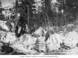 Camp showing tent and piles of supplies, White Pass Trail, ca. 1898
