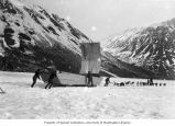 Men and dogsled navigating large sled with sail on Windy Arm, Tagish Lake, ca. 1898