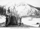 Two men setting up tent on Windy Arm of Tagish Lake with sled with sail in the background, ca. 1898
