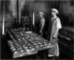 Two women at Apex Fish Co., Anacortes, preparing cans for steam cooker, 1913.