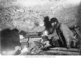 Two men, identified as Gorst and Ainsworth, building a fire in a mine shaft to thaw the frozen...