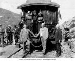 Members of the Seattle Chamber of Commerce posing on caboose of train along the mile 17 of the...