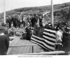 Members of the Seattle Chamber of Commerce raising the United States flag at the border between...