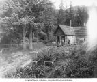 Two men standing in front of a cabin surrounded by garden, Haines, ca. 1914
