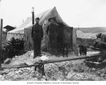 Two men standing outside tent showing mining dump in background, Gold Hill, ca. 1898