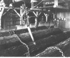 Interior of Moran Brothers Co. sawmill, Seattle, loading saw carriage.