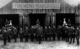 Firemen and equipment posed outside wooden building with temporary banner over doors, 1889.