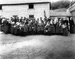Native children in school uniforms holding American flags, Holy Cross, Alaska.