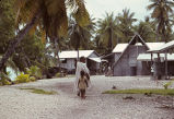 Village scene showing native woman with child, Rongelap Island, August 24, 1964