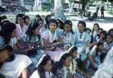 Native women and children playing guitar and singing, Likiep Atoll, August 20, 1949