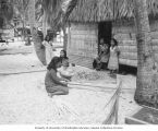 Native women in front of their home weaving palm branches, Rongerik Island, 1947