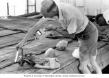 Kelshaw Bonham taking radiation readings from a crab from various angles, Bikini Atoll, Summer 1964