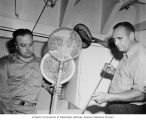 Scientists Robert Meigs and Clarence Pautzke checking over the equipment they will use at Bikini,...