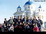 Group of young tourists in front of an Orthodox church in the village of Volzhskiy