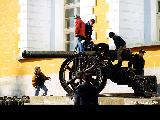 Children climbing on  a cannon inside the Kremlin in Moscow
