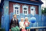 Grandmother with her granddaughters in front of their house in the village of Yermilovo