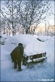 Man digging out a car after a big snowfall in Petropavlovsk-Kamchatsky