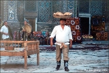 Man offering non (traditional bread) during a dance performance in the Registan Plaza's Medressa...