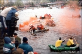 Tartu University students racing boats on the Emajogi River, complete with colored smoke bombs.