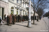 People standing in a long line waiting for a dairy store to open, in Odessa