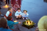 Children looking at a wreath lit with candles at the Jonines midsummer festival in Vilnius
