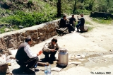 Karachay men filling a bucket and bottles with Narzan, a mineral water, by the Indysh River