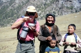 Kyrgyz family and a tourist eating a gift of yoghurt
