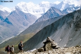 Hikers near a stone pile on Tekeliu Ridge, looking onto Mount Belukha, Altai Mountains