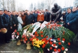 People and flowers in front of the  Monument to the Grieving Soldier