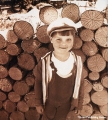 Boy standing next to a stack of firewood in the Komi Republic