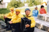 Accordionist and two men from a folk troupe resting on steps, Komi Republic