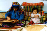 Grandmother and her granddaughter separating grain from impurities in Sahvron