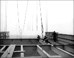Workmen fastening rope to a beam during salvage operations on the Tacoma Narrows Bridge, ca. 1941