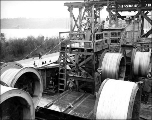 Tacoma Narrows Bridge construction showing machine spinning suspension cable, ca. 1940
